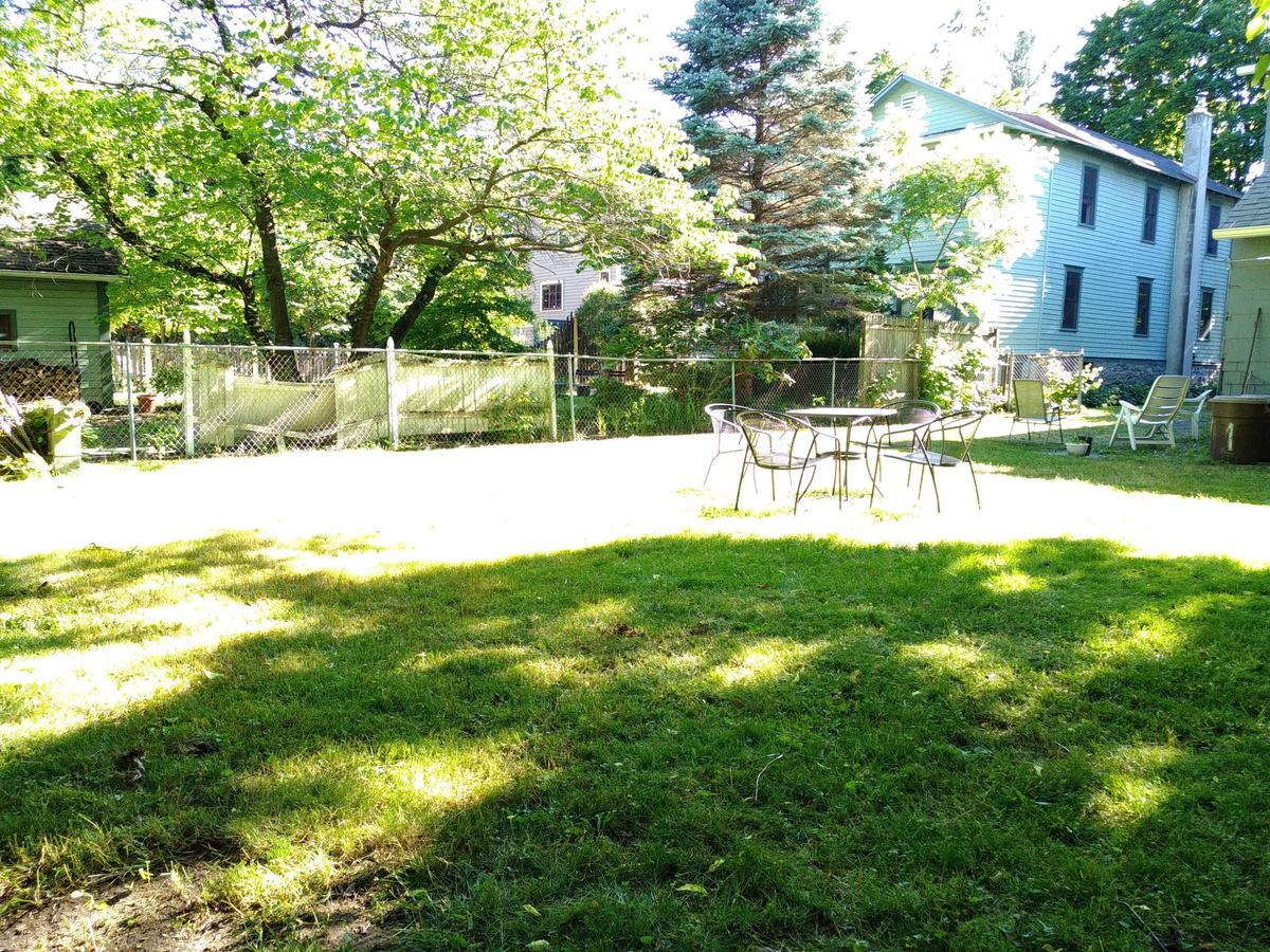 Large fenced-in backyard with patio furniture